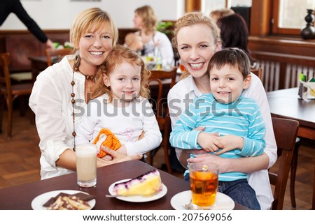 Beautiful portrait of two happy smiling young mothers with their small children sitting on their laps enjoying drinks and cake at a restaurant table - stock photo