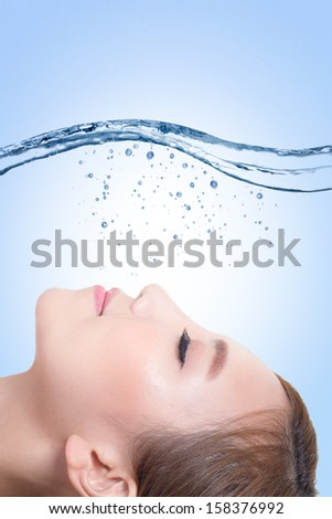 Beautiful portrait of woman with fresh skin in splashes of water , concept for beauty skin care isolated on blue background, asian model - stock photo