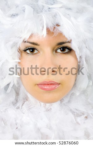 Beautiful portrait of young woman surrounded by feathers - stock photo