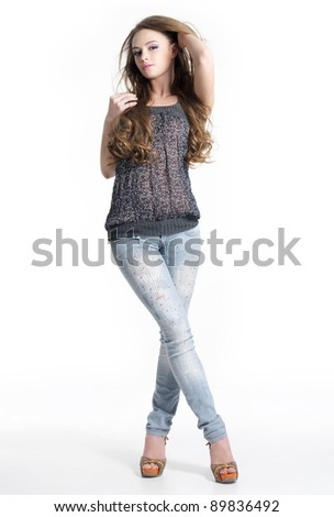 Beautiful posing young woman in jeans - isolated on white background. Full length portrait