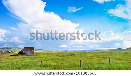 Beautiful prairie landscape with old barn and blue sky and clouds in Alberta, Canada