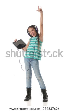 Beautiful pre-teen girl dancing and going crazy using a tablet computer and headphones - stock photo