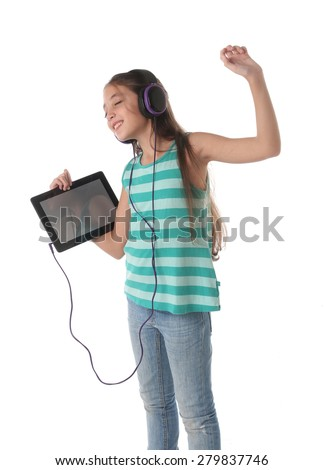 Beautiful pre-teen girl dancing with a tablet and headphones. Isolated