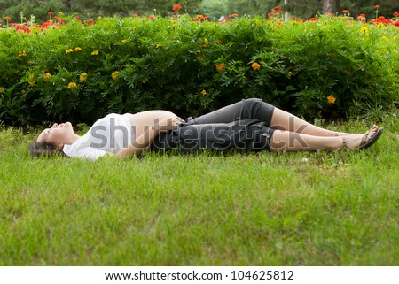 Beautiful pregnant asian woman relaxing in summer park