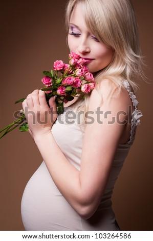 Beautiful pregnant blond woman , a studio portrait. - stock photo