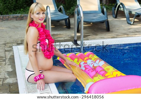 Beautiful pregnant blonde girl is sitting with colorful mattress and hawaiian flowers near blue water of swimming pool