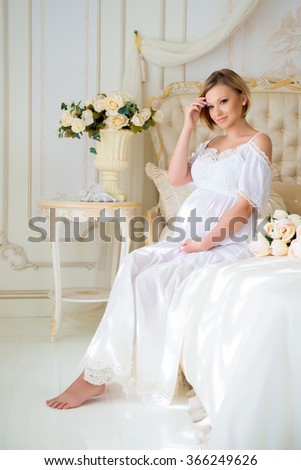 Beautiful pregnant girl in a home clothes sitting in the interior on a bed of roses - stock photo