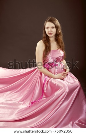 beautiful pregnant girl in a pink dress - stock photo