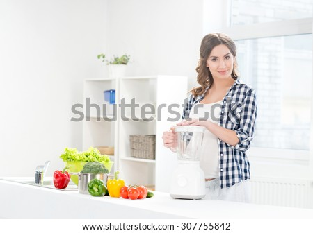 Beautiful pregnant smiling woman cooking with a blender. - stock photo