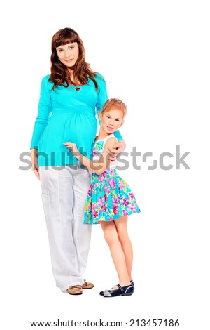 Beautiful pregnant woman and her adorable daughter expecting one more baby. Isolated over white. - stock photo