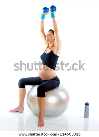 Beautiful pregnant woman at fitness gym with toning balls on aerobics - stock photo