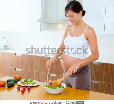 Beautiful pregnant woman at home kitchen preparing salad