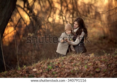 beautiful pregnant woman brunette with her infant daughter little girl sitting in the park or forest and playing with each other at autumn - stock photo