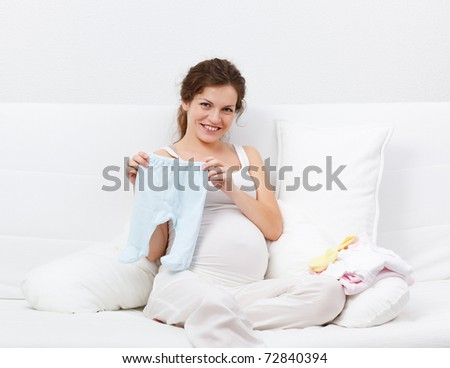Beautiful pregnant woman choosing baby's clothes - stock photo