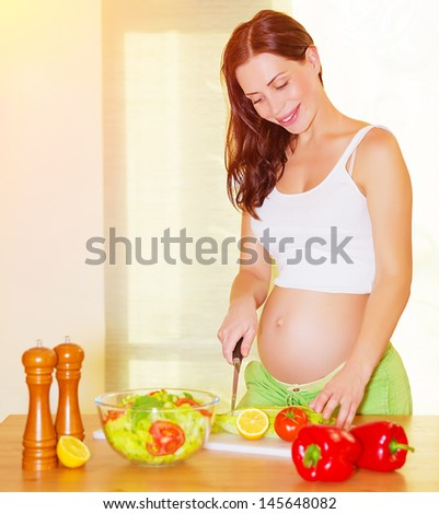 Beautiful pregnant woman cooking salad on the kitchen at home, healthy nutrition, cutting vegetables, happy and healthy pregnancy concept - stock photo