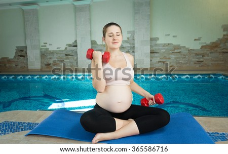 Beautiful pregnant woman doing exercise with dumbbells near swimming pool - stock photo