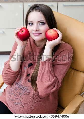 Beautiful pregnant woman eat apple. Indoor photo. - stock photo
