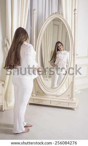 beautiful pregnant woman European standing in the room, in the bedroom, holding a small child blouse smiling and looking in the mirror, - stock photo