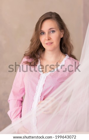 Beautiful pregnant woman in anticipation near the window - stock photo