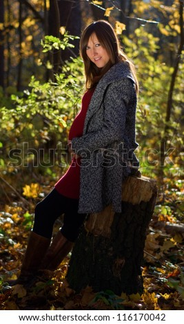 Beautiful pregnant woman in autumn forest