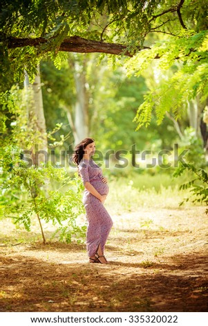 Beautiful pregnant woman in green garden