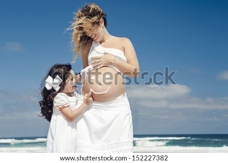 Beautiful pregnant woman in the beach with her little daugther making a smile on mom's belly with sunscreen - stock photo