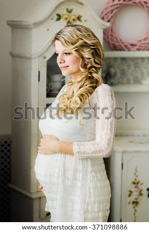 Beautiful pregnant woman in white dress caressing her belly in white room. Sensual photo. - stock photo