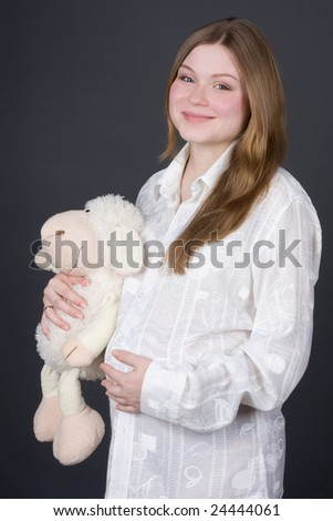 beautiful pregnant woman in white holding toy on grey background - stock photo