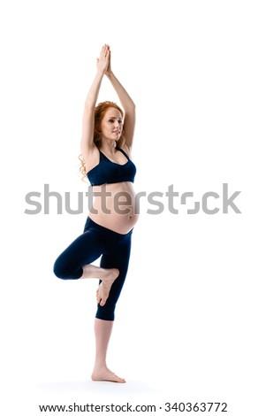 Beautiful pregnant woman in yoga pose - stock photo