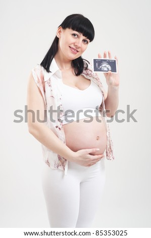 Beautiful pregnant woman is holding a photo of her Ultrasound - stock photo