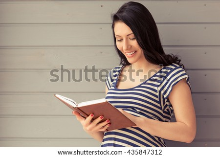 Beautiful pregnant woman is reading a book and smiling while standing against gray wall
