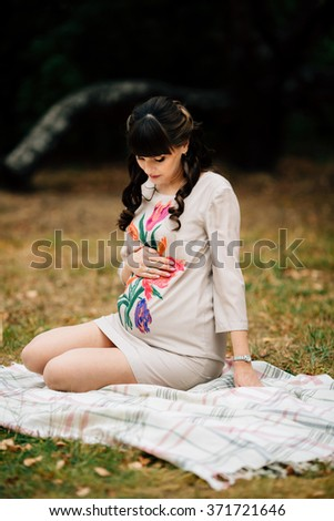 Beautiful pregnant woman is sitting and looking lovely on tummy on the checkered blanket with her hand on belly. Autumn picnic.
