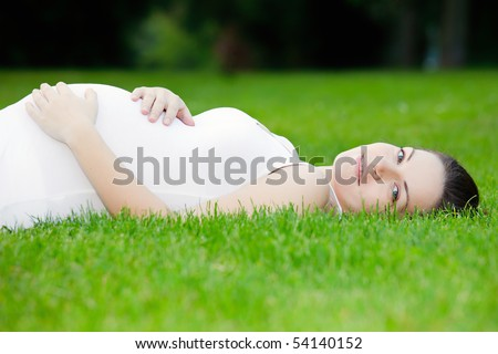 Beautiful pregnant woman laying on grass - stock photo