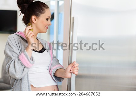 Beautiful pregnant woman loking for food - stock photo