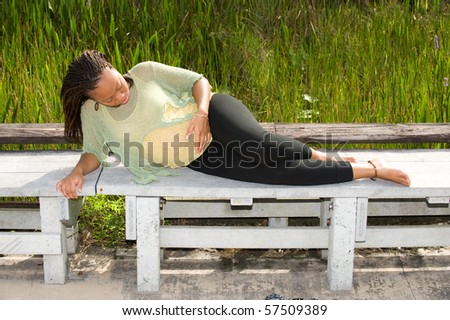 Beautiful pregnant woman lying outside at a park - stock photo