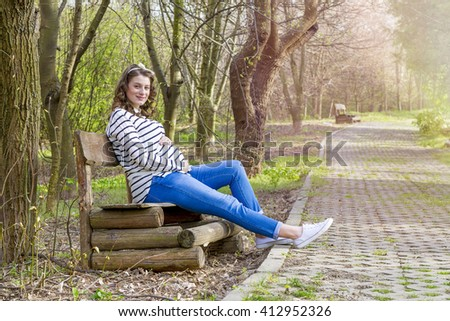 Beautiful pregnant woman outdoor in the park on bench - stock photo