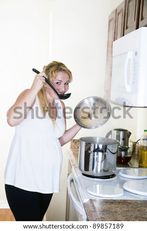 Beautiful pregnant woman prepares the soup on the electric stove