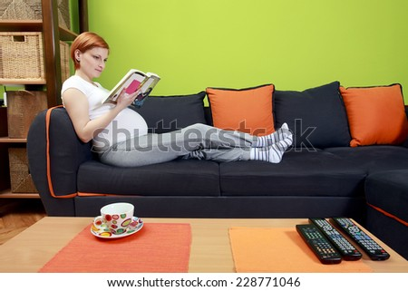 Beautiful pregnant woman reading a book - stock photo