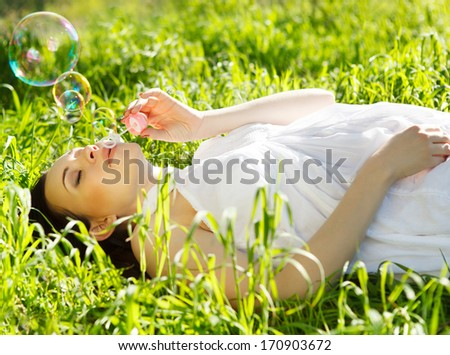 Beautiful pregnant woman relaxing on grass in the spring park