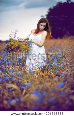 Beautiful pregnant woman relaxing outside in the fields - stock photo