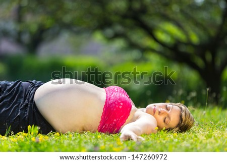 Beautiful pregnant woman relaxing outside in the park
