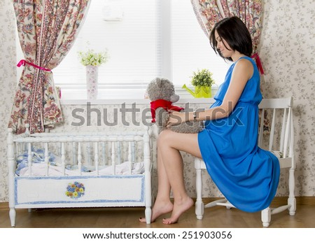 beautiful pregnant woman sitting near the cot with a soft teddy bear in hand - stock photo