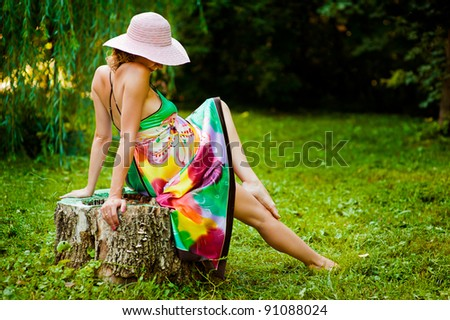 Beautiful pregnant woman sitting on stump in green park - stock photo