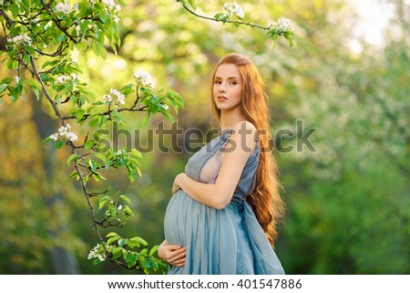Beautiful pregnant woman standing among trees, outdoor in nature. - stock photo