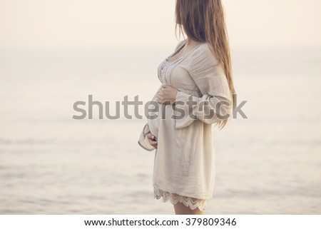 beautiful pregnant woman standing on the beach - stock photo