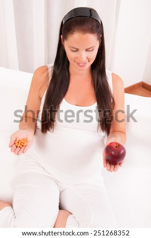 Beautiful pregnant woman with an apple in one hand and vitamins in another - stock photo