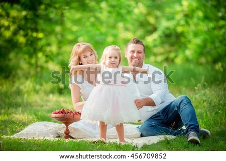 Beautiful pregnant woman with her husband and young daughter in green garden - stock photo