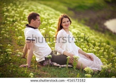 Beautiful pregnant woman with her husband in green garden