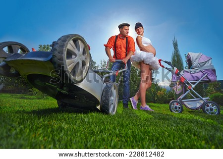 Beautiful pregnant woman  with her husband near country house. - stock photo