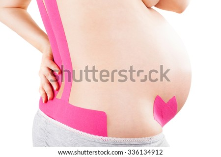 Beautiful pregnant woman with kinesio tape on her back. Back pain in pregnancy, alternative kinesio tape therapy. - stock photo